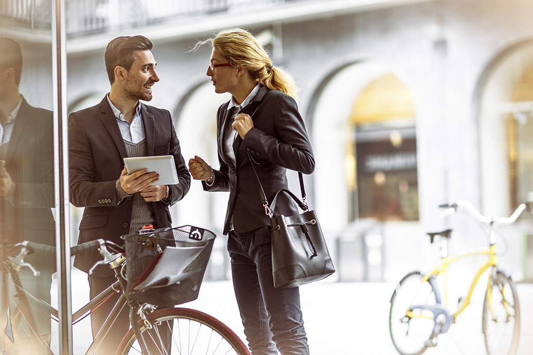 cheerful-businessman-with-bicycle-and-his-colleague-comunicating